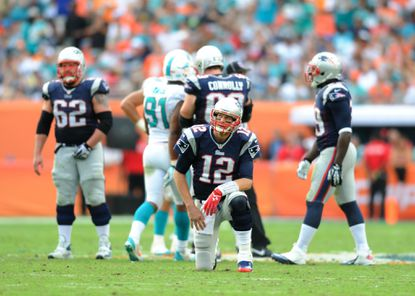 Patriots quarterback Tom Brady reacts after being sacked by the Miami Dolphins.