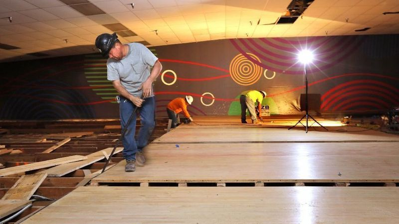 In this file photos, workers dismantle the maple wood bowling lane approach surfaces at the Vista Entertainment Center bowling alley. At left were bowling lanes of hard pine boards that have been removed.