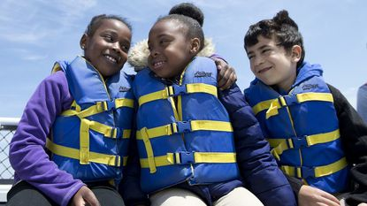 Simone Brocht puts her arm around classmate Ma'Kayla Cromartie as they and fellow first-grader Jackson Vijayan ride in a boat to Poplar Island on April 23. The Green School of Baltimore students released two terrapins, Pluto and Hidey Hermit Crab, they had been caring for.