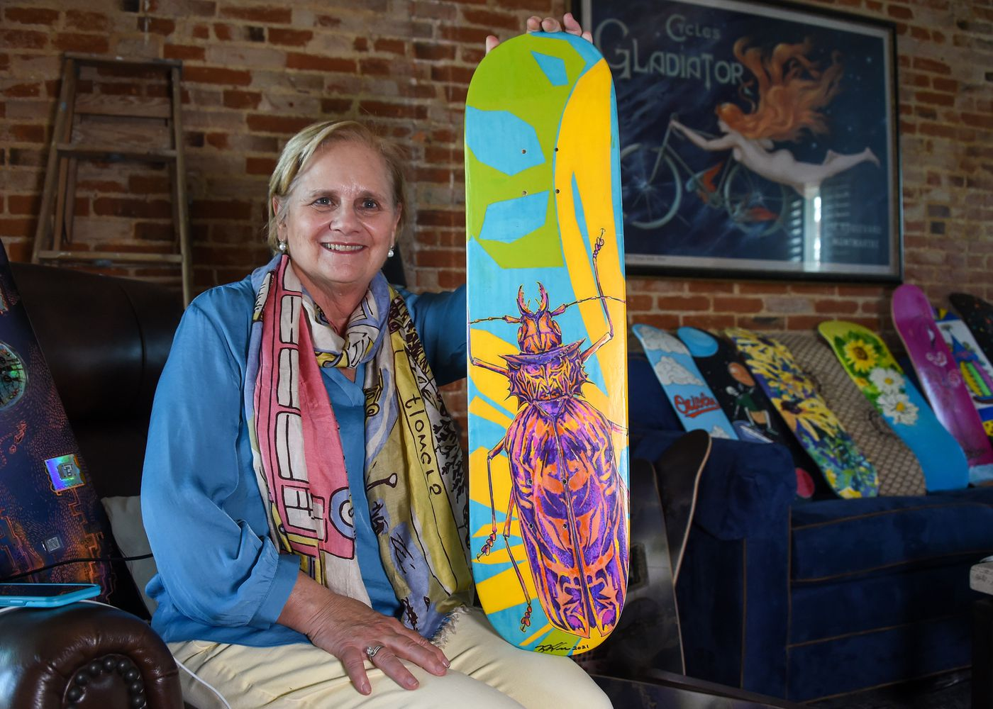 """""""Nothing Bugs Me"""" painted by Wrae Wene is held by Cindy Conklin on Wednesday, April 7, 2021; the art piece will be auctioned off to help fund the completion of Jake's Skate Park at Rash Field."""