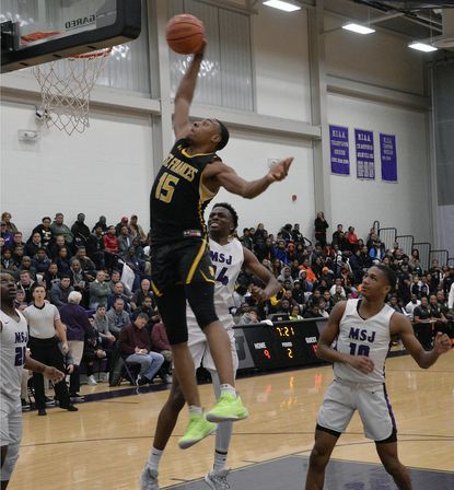 St. Frances's Jamal West , right, dunks as several Mount St. Joseph Gaels players look on in the first half of the Baltimore Catholic League basketball game. Mount St. Joe's defeated St. Frances 62-53 at the Smith Center.