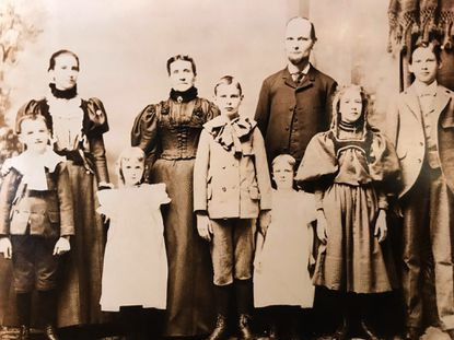 The photo, taken about 1900, shows the family of Agnes Bosse, the girl dressed in white, third from the left. Her father, Joseph Bosse (the tall bald man in the back) and his wife are surrounded by their children. They lived in South Baltimore on Light Street.