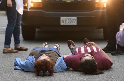 A pair of Hopkins students lay in the road in front of a police van carrying fellow protesters. Seven people were arrested after authorities ended a monthlong sit-in at Garland Hall on Johns Hopkins' Homewood campus last May.