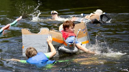 Nick Moss, left, of Highland and James Weidemann, right, 12, of Ellicott City try to beat the counselor cardboard boat at the turn at Camp Whippoorwill in Pasadena on Aug. 2.