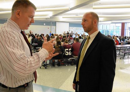 School Security Chief Duane Williams (right) chats with Winters Mill High School principal Eric King as students learn about academy choices.
