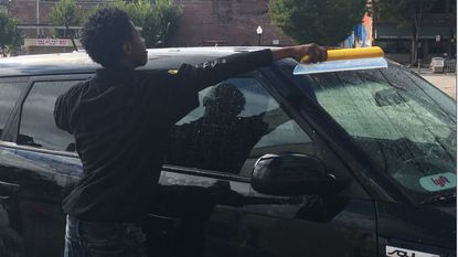 A Squeegee Corps members works Saturday at a pop-up car wash in Station North.