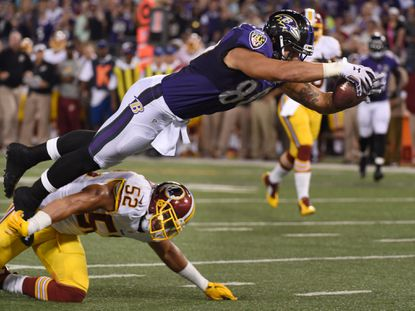 Ravens tight end Crockett Gilmore, top, leaps over Redskins' Keenan Robinson, right, to dive into the end zone in the first quarter. The scoring play was nullified by a penalty in the Ravens' preseason loss to the Redskinsat M&T Bank Stadium.