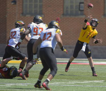 Maryland quarterback Perry Hills, right, gets off a pass during the Red-White spring football game at Byrd Stadium.