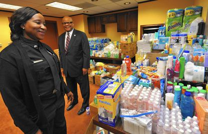 Masa M. Salifu, left, a corrections officer at Baltimore Central Booking Intake Center, initiated a donation drive for supplies for Ebola patients and workers in West Africa. Regional executive director Wendell M. France (behind her), from the Department of Public Safety and Correctional Services, supported the drive, in which BCPIC employees donated water, electrolytes, bleach tablets, sanitizers and other cleaning supplies.
