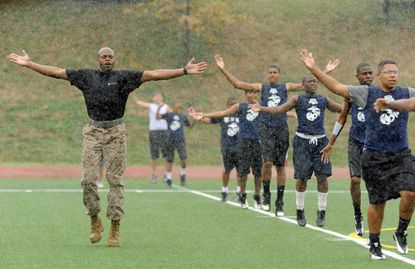 Marine Staff Sgt. Jamal Queen, of Baltimore, leads Diamond Flight Football Camp participants in exercises while a steady rain falls on the field at Mount St. Joseph.