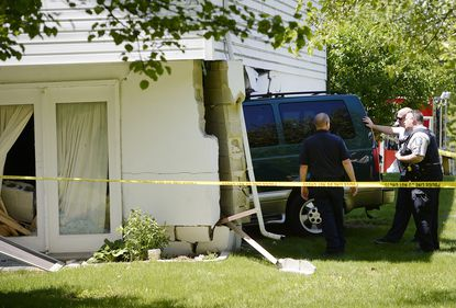 Responders assess the scene of an accident where a van crashed into the side of house at the corner of Daniel Drive and Whispering Meadow Court in Westminster Wednesday, May 12, 2021.