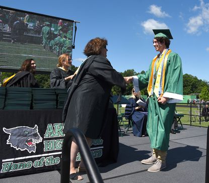 Arundel High School Principal Gina Davenport presents 2019 valedictorian Richard Osikowics with his diploma. In two years, Anne Arundel high schools will stop naming valedictorians based on their grade point averages.