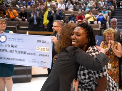 Students and others in attendance cheer and the clap congratulates Erin Wyatt, right, an eighth grade science teacher at North Harford Middle School after she received the prestigious Milken Educator Award Wednesday morning during a assembly at North Harford Middle School.