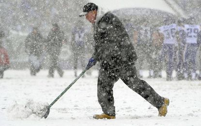 A member of the field crew shovels to expose the yard lines between plays during the first quarter of the Ravens-Vikings game at M&T Bank Stadium.