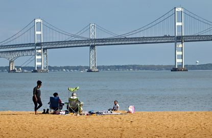 A family enjoys an afternoon on the beach at Sandy Point State Park last April when afternoon temperatures reached into the 60s. April 13, 2021. (Jeffrey F. Bill/Capital Gazette).
