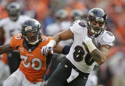 Denver Broncos strong safety David Bruton, left, can't get a hold of Ravens tight end Crockett Gillmore during the second half Sunday, Sept. 13, 2015, in Denver.