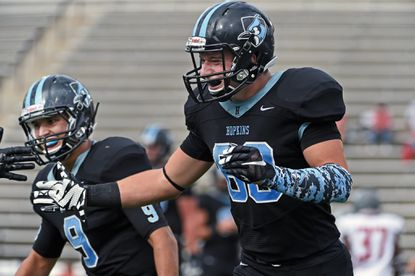 Johns Hopkins wide receiver Quinn Donaldson, right, celebrates his second touchdown catch of the game for the go-ahead score in the fourth quarter. On left is quarterback Jonathan Germano, who threw four TDs in the game.