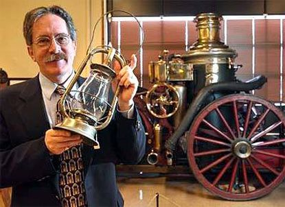 Stephen Heaver of the Fire Museum of Maryland holds a lantern that was used on an antique steam pumper (background) used to fight the Great Baltimore Fire of 1904.