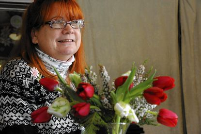 Libby Francis-Baxter, owner of The Modest Florist, sits near an arrangement of tulips, heather and Leyland cypress in Hampden last week. Francis-Baxter offers local flowers, not roses, even around Valentine's Day.