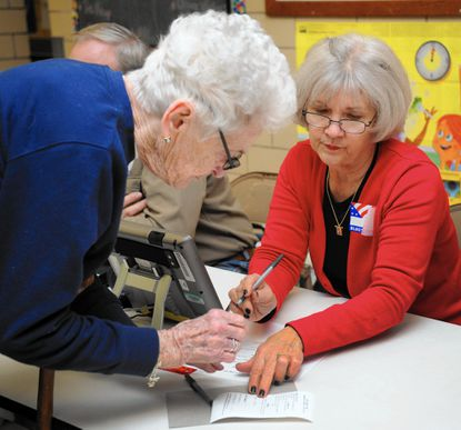 Election judge Joanne McAuley, right, helps voter Genevieve Snodgrass get checked in before casting her vote at Havre de Grace Elementary School Tuesday afternoon.