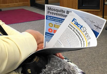 A woman holds multiple fact sheets on the Zika virus and other mosquito-borne diseases during a town hall meeting in Bel Air Monday on preventing Zika.