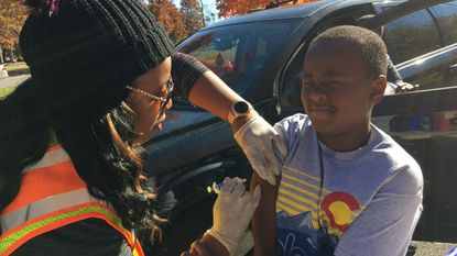 Josh McCullough, 8, grimaces as his mother, Daishon McCullough, a surgery team unit manager at MedStar Health Franklin Square Medical Center, gave him a flu shot Sunday at the hospital's free vaccine giveaway. Staff gave out more than 800 vaccines throughout the day.