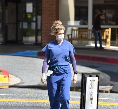 A University of Maryland Upper Chesapeake Harford Memorial Hospital employee wears a mask as she makes her way to a training exercise in Havre de Grace Tuesday afternoon. Hospitals, clinics and doctor's offices are taking extra precautions when treating patients.