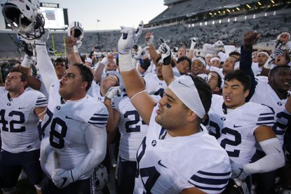 "This Oct. 8, 2016, file photo shows BYU players, including Austin Heder (42), Tuni Kanuch (78), Kesni Tausinga (94) and Hiva Lee, right, celebrate following a 31-14 win over Michigan State. Navy AD Chet Gladchuk said he called BYU athletic director Tom Holmoe minutes after the cancelation of the Notre Dame game and ""grabbed that game immediately."""