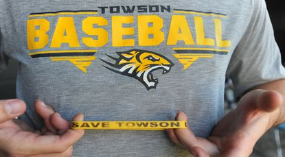 """Towson University baseball players are wearing yellow wristbands with """"Save Towson baseball"""" printed on them."""