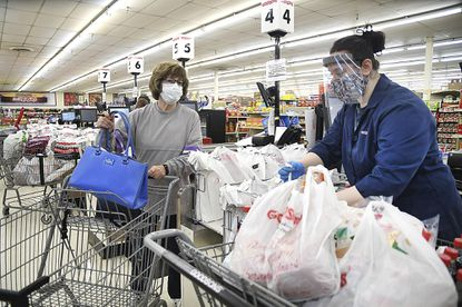 Delores Browning, left, waits for Molly Stanley to bag her groceries at Goodson's Supermarket in Oceana, W.Va. Single-use plastic bags have become the standard at grocery stores where clerks decline to handle bags that customers bring to the store for fear they may be compromised during the coronavirus pandemic. (Rick Barbero/The Register-Herald via AP)