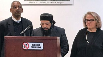 Sheikh Omar Baloch, imam of the Masjid Al Falaah mosque in Abingdon, is with the Rev. Baron Young, left, and Rabbi Gila Ruskin while reading a communique signed by all three during an interfaith service Sunday to remember the victims of mass shootings at mosques in New Zealand.