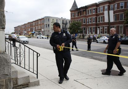 Baltimore Police investigate the scene where a man was shot in the chest July 27near North Avenue and Carey Street.