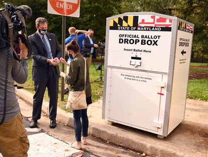 """Baltimore County executive Johnny Olszewski, Jr. hands an """"I Voted"""" sticker to his senior advisor Samantha O'Neil after both cast their ballots in an official drop box on the campus of Towson University, on Wednesday, Oct. 21."""