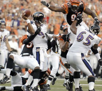 Ravens quarterback Steve McNair tries to throw under heavy pressure from the Cincinnati Bengals' defense in the first quarter. McNair lost three fumbles, threw an interception and left with a groin injury.