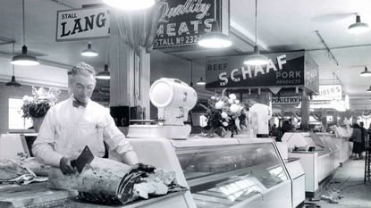 George C. Romoser cuts meat at his stall at Cross Street Market in November 1952.
