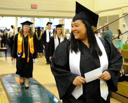 Lisa Concon smiles for a photo as she enters the gymnasium during Carroll Community College's graduation ceremony at McDaniel College in Westminster Wednesday.