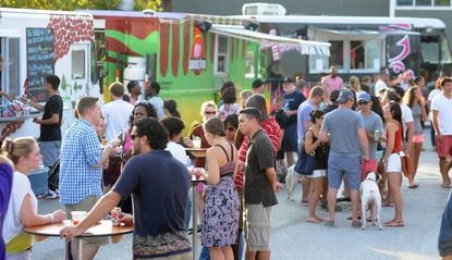 Food trucks and customers at a traveling food truck rally called The Gathering.