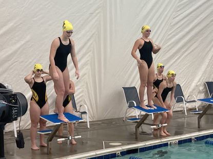 Members of the John Carrol girls swim team prepare to enter the pool during a relay in Wednesday night's meet.