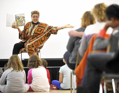 """Sandymount Elementary teacher Nira C. Taru reads from the book """"Child of the Civil Rights Movement"""" by Paula Young Shelton and Raul Colon during """"A Day On, Not a Day Off,"""" an observation of Martin Luther King Jr. Day, at McDaniel College in Westminster Monday, Jan 19, 2015."""