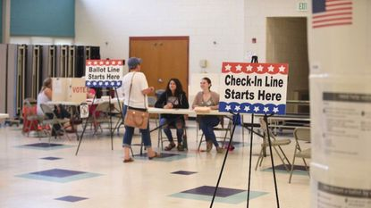 A voter checks in at the polls at Elkridge Elementary School on primary election day June 26.