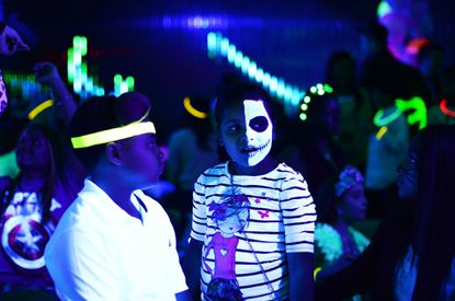 Kids wearing Halloween costumes and makeups join an electronic dance music party organized by CirKiz at a night club in New York.