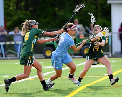 C. Milton Wright's Heather McKee splits the North Harford defense, Leah Monticwllo, left, and Hannah Kehring, and drives to the goal during Wednesday's regional championship game at C. Milton Wright.