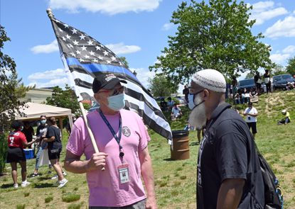 """District 1 Laurel City Council member Carl DeWalt, left, speaks with former Laurel mayoral candidate Jeff Mills on Sunday before the """"Laurel Stands for Justice, Black Lives Matter"""" rally in Granville Gude Park. DeWalt was booed off the stage when he went to speak holding a """"Thin Blue Line"""" American flag that was designed to show support for law enforcement but has also been used at times in white supremacist marches."""
