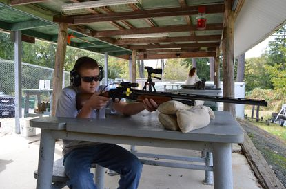 Cody Mulligan, 14, takes aims at the shooting range at the Baltimore County Game and Fish Rifle Range with the guidance of his stepfather, Gerald Hessler.
