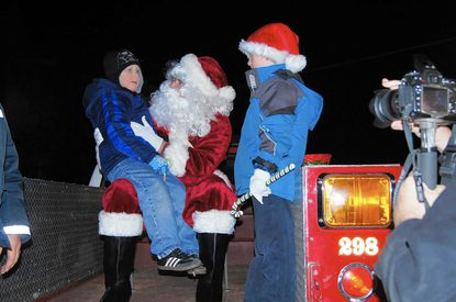 Santa (aka Will Hill), talks Christmas list with Nicholas as Ethan Hill, Santa's son, looks on during Campus Hill's tree lighting ceremony in 2013.
