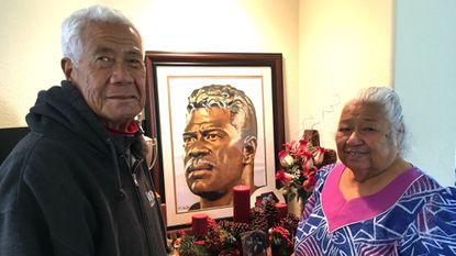 Tiaina Seau (left) and Luisa Seau pose at their home in front of artwork of their son, Junior Seau.
