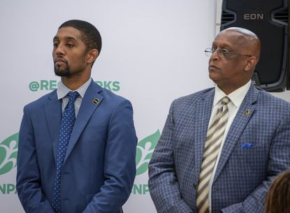 "Baltimore City Council President Brandon Scott (left) and Mayor Bernard C. ""Jack"" Young disagree about whether to spend a city surplus to add heating and air conditioning at city schools."