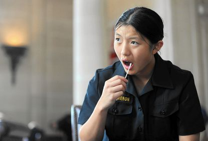 Naval Academy Midshipman Elizabeth Cameron takes a swab of the inside of her cheek for information as a potential bone marrow donor.