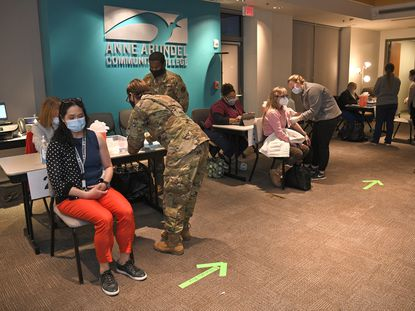 The Maryland National Guard helps Anne Arundel County Heath Department staff give out the Pfizer COVID-19 vaccine to Phase 1A and 1B recipients at a clinic held at the Anne Arundel Community College, Monday, January 18, 2021. (Paul W. Gillespie/Capital Gazette).