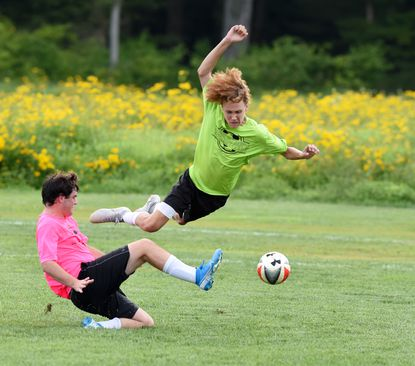 Pink team's Dylan Ginski makes the slide tackle on Lime's Quinnten Hatfield during the opening day match ups of the Harford Boys Soccer League at the Carsin's Run fields Wednesday evening.